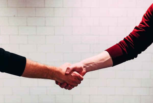 Photo of two people shaking hands in business deal.