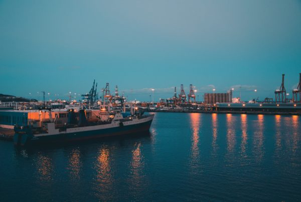 Photo of container ships at shipping port at dusk